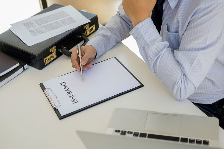 Midsection Of Insurance Agent Writing On Form At Office