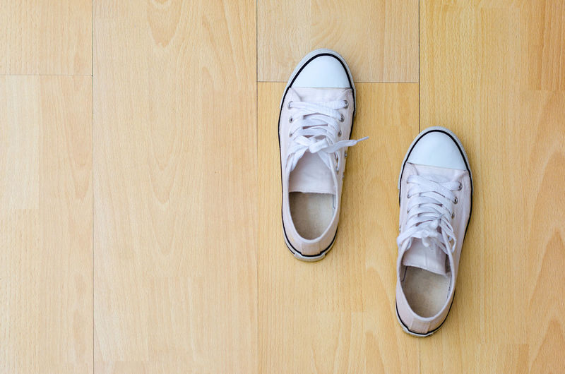Directly above shot of white canvas shoes on hardwood floor