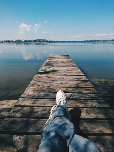 Low section of man lying on jetty in lake against sky