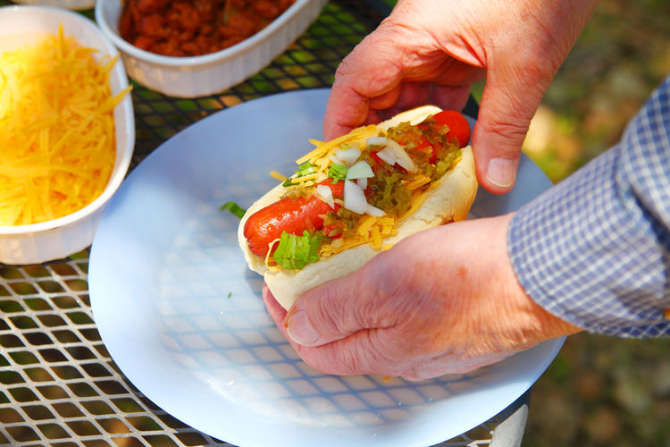 Man holds hot dog with cheese, relish, onions