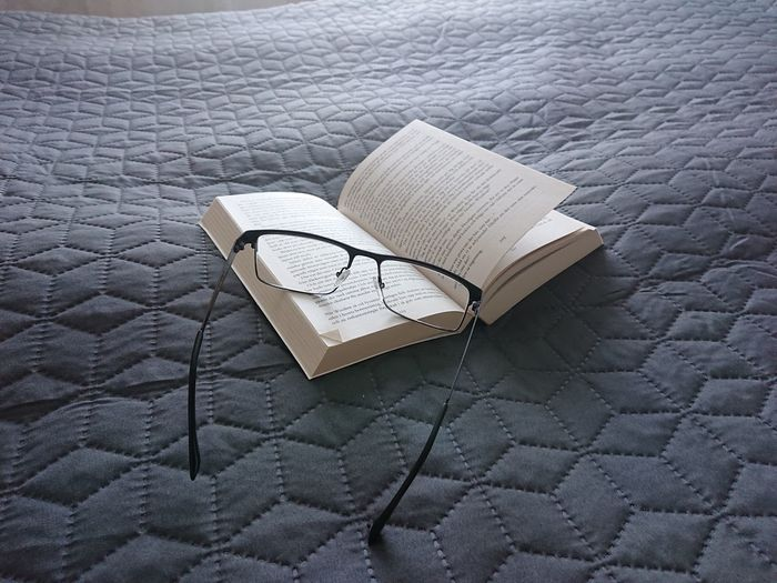 High angle view of open book on bed