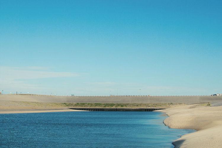 View of calm beach against blue sky