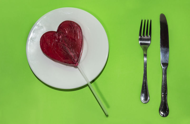 Red heart lollipop ready to eat on a white plate with stainless steel fork and knife, on green background. Indoors  No People Studio Shot Backgrounds Copy Space Wallpapaer Heart Shape Lollipop Red In Love Romance Romantic Celebrate Celebration Object Colorful Fun Tasty Delicious Green Plate Fork Knife White