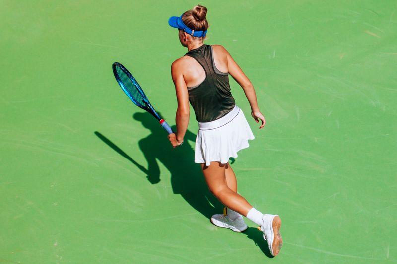 Female tennis player, holding racket, shadow