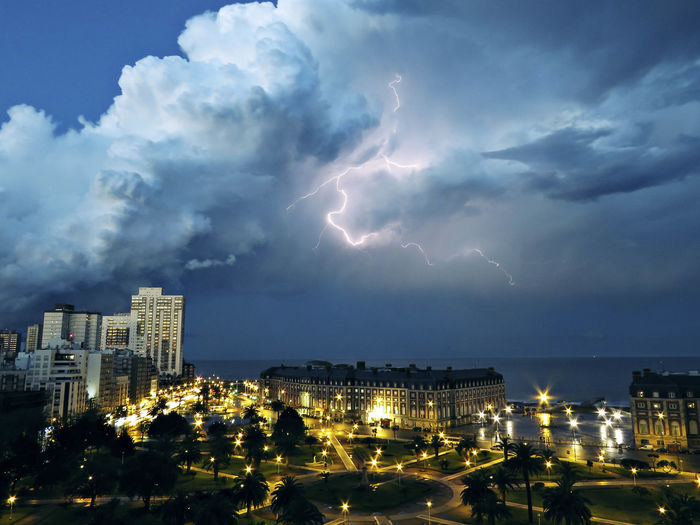Lightning Over City Buildings Against Storm Clouds