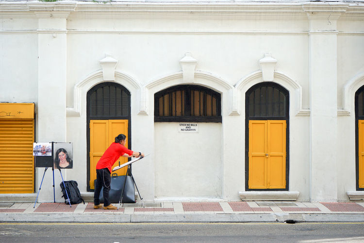 KUALA LUMPUR, MALAYSIA - April 12, 2015: Men artist painting on the street. A street artist in the old town. Image contain certain grain or noise and soft focus. Adult Adults Only Arch Architecture Artist Artist Painting Building Building Exterior Built Structure City Day Full Length Kuala Lumpur Men Old House Outdoors Painting People Road Street Artist Travel Two People