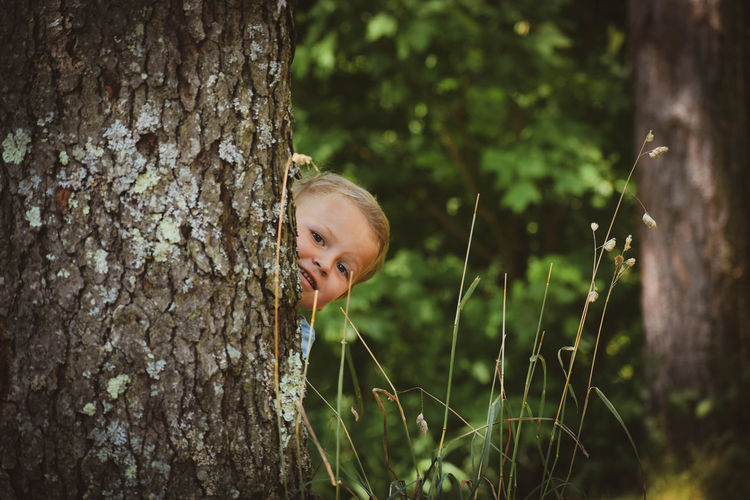 Portrait of a smiling boy behind tree
