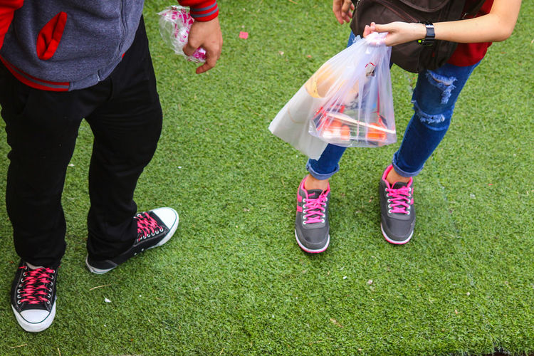 EyeEm Selects Vibrant Colors Colorful Outfit Pink Shoe Laces Human Leg Shoes Low Section Limb Two People Togetherness Leisure Activity Grass Green Color Standing Fun Casual Clothing Lifestyle Multi Colored Couple - Relationship Fun Dating Neon Life