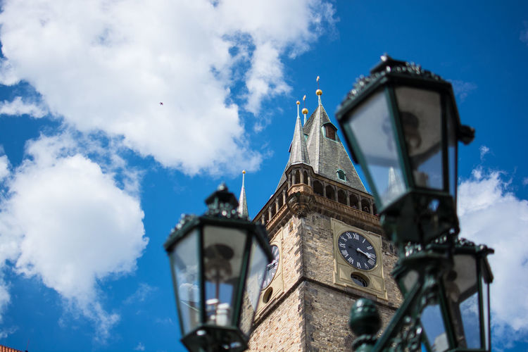 Low angle view of gas lights and prague astronomical clock against sky