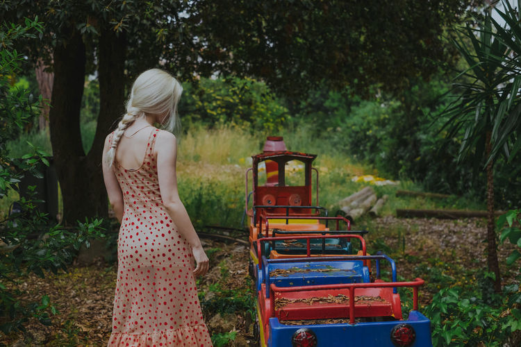 Rear view of young woman standing by miniature train at park