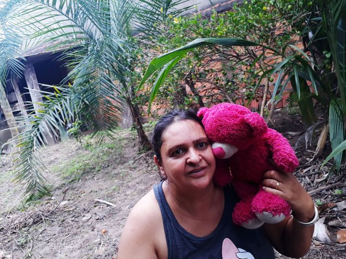 Portrait of smiling woman with teddy bear outdoors