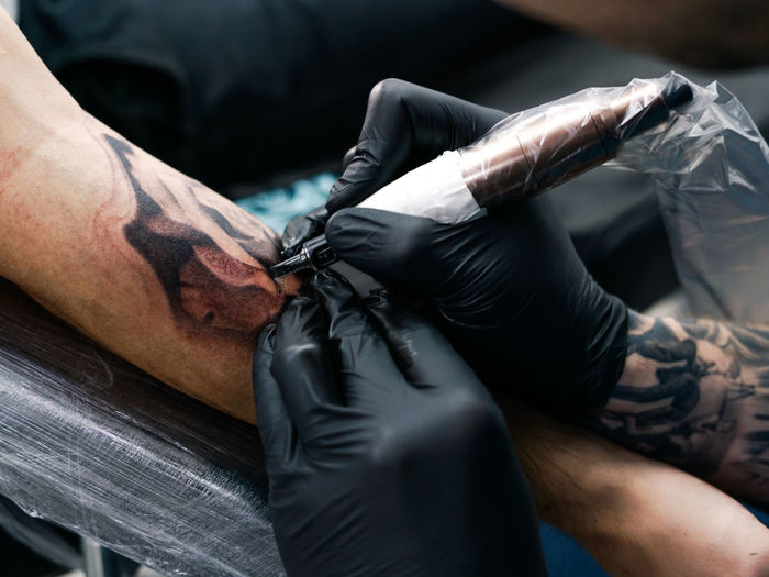 tattoo session Tattoo Hand Real People Human Hand Men Human Body Part Creativity Indoors  Tattooing Working Midsection Occupation Protective Glove Art And Craft Fashion Skill  Expertise Leather