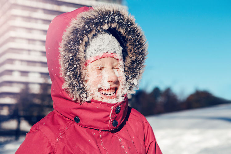 Close-up of cheerful girl with snow covered face