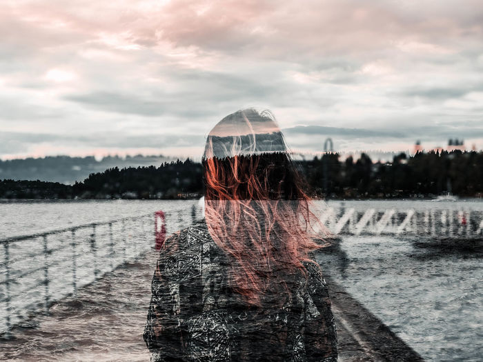 Double exposure image of woman with sea against sky