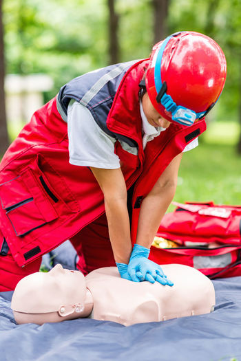 Healthcare worker practicing on cpr dummy at park