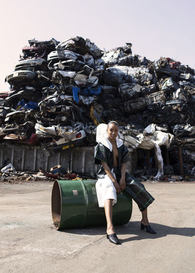 Full length of young woman with garbage against sky