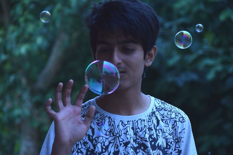 Close-up of boy playing with bubbles