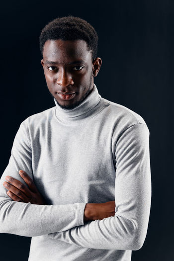 Portrait of young man against black background