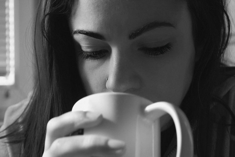 Close-up of young woman with coffee cup