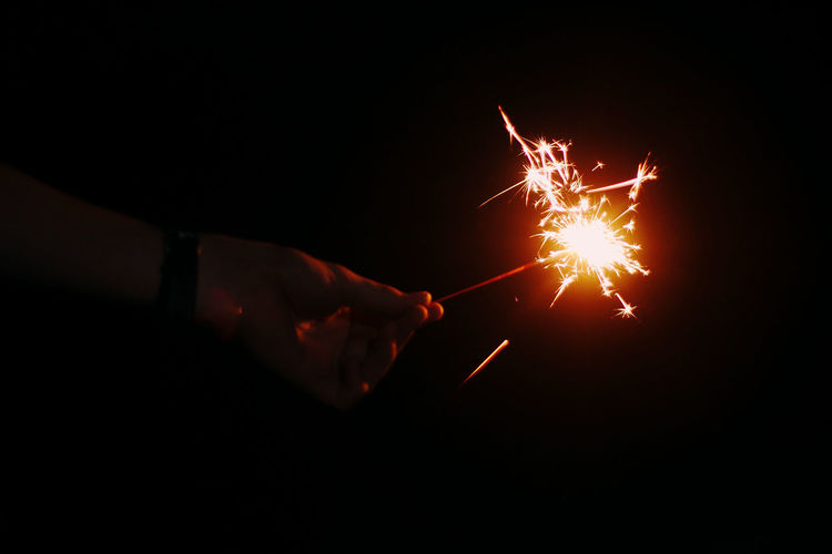 Cropped hand of person holding illuminated sparkler during night