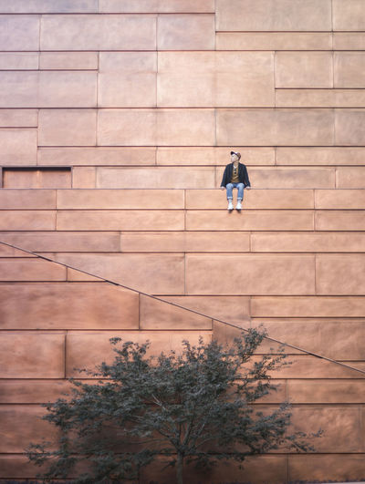 Low angle view of man sitting on building