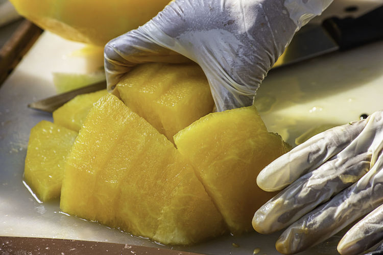 Hand holding yellow watermelon And use a knife to cut a piece. Freshness Food Food And Drink Healthy Eating Wellbeing Close-up Indoors  Fruit Yellow Still Life SLICE No People Preparation  Focus On Foreground Table Tropical Fruit Citrus Fruit Day High Angle View Organic Snack
