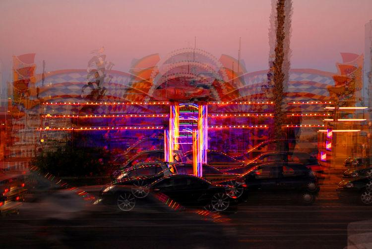 Blurred image of car and illuminated amusement park