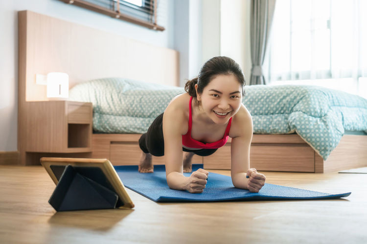 Portrait of smiling woman exercising at home