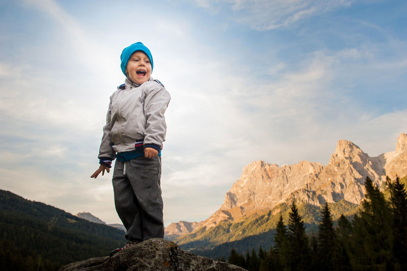 Low angle view of boy standing on mountain against sky