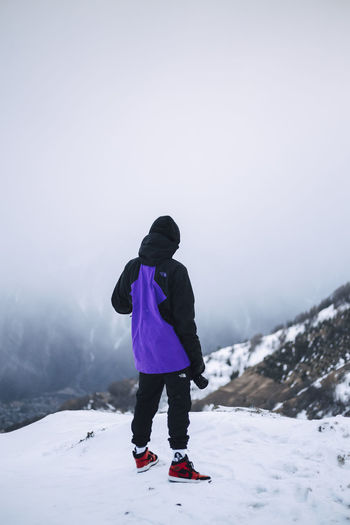 Rear view of boy standing on snow against mountain