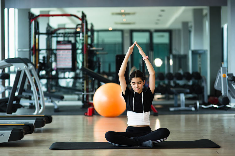 Full length of girl meditating at gym