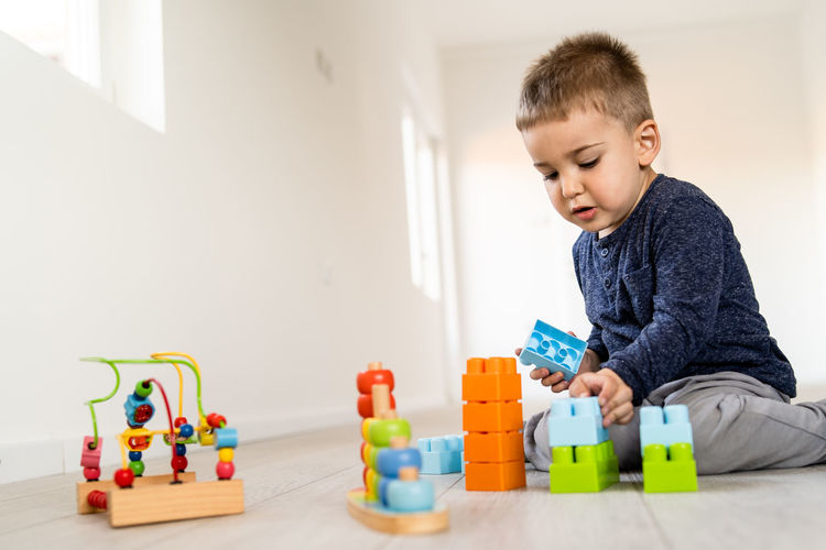 Childhood Child Multi Colored Toy Indoors  Toy Block Boys Real People One Person Men Males  Innocence Casual Clothing Leisure Activity Lifestyles Home Interior Learning Cute Playing