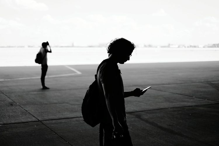 Side view of man using mobile phone at tempelhof airport