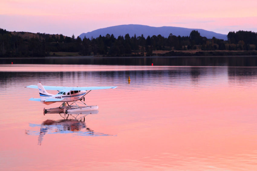 A seaplane reflected in the water Plane Reflection Sea Plane Aircraft Airplane Beauty In Nature Day Lake Moored Nature Nautical Vessel No People Orange Color Outdoors Reflection Scenics Sky Sunset Tranquility Transportation Tree Water