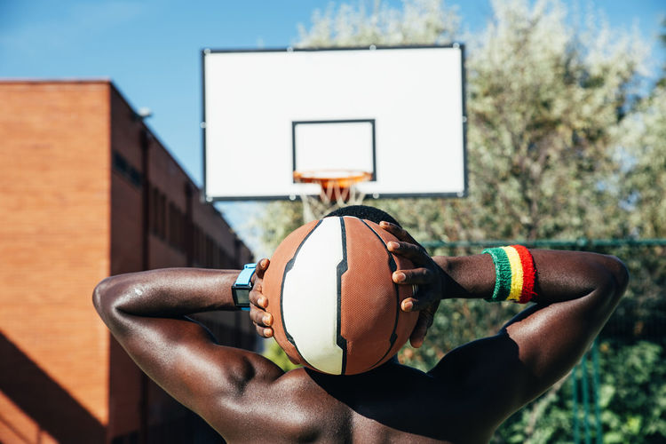 Rear view of man holding ball against basketball hoop