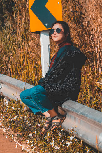 Full length of woman sitting on railing by road