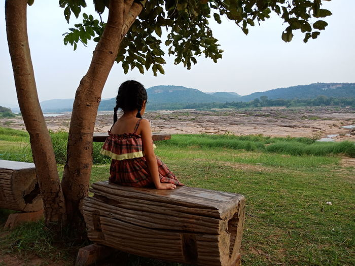 Girl sitting on seat by tree against sky
