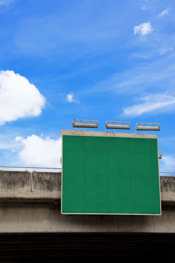 Low angle view of billboard against blue sky
