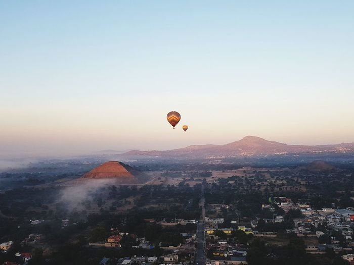 Hot air balloons flying over misty city against sky during sunrise