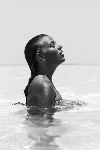 Side view of woman in water against sky