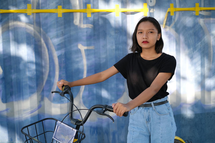 Cute girl holding bicycle standing against wall outdoors