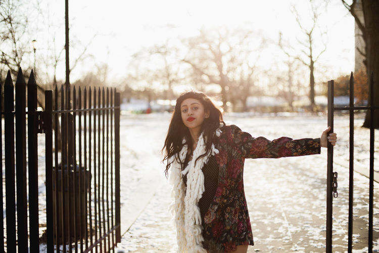 Full length of woman standing in park during winter