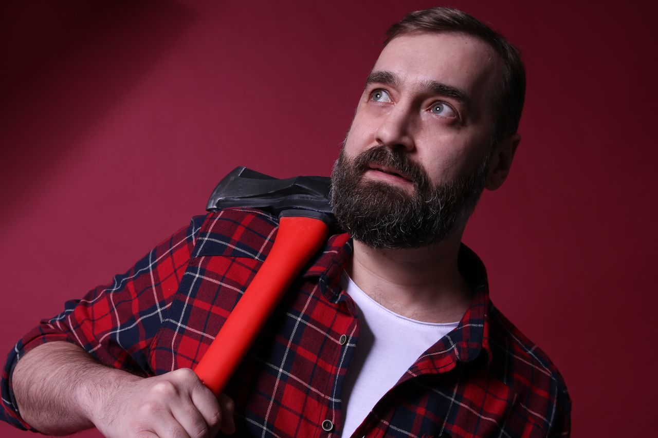 Lumberjack With Axe Looking Away While Standing Against Red Background