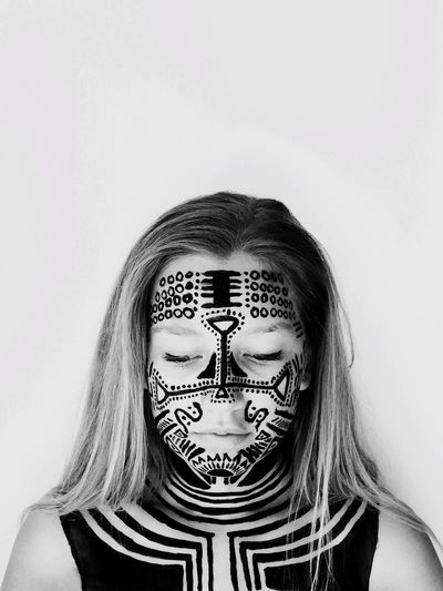Portrait Of Young Woman Wearing Face Paint Against White Background