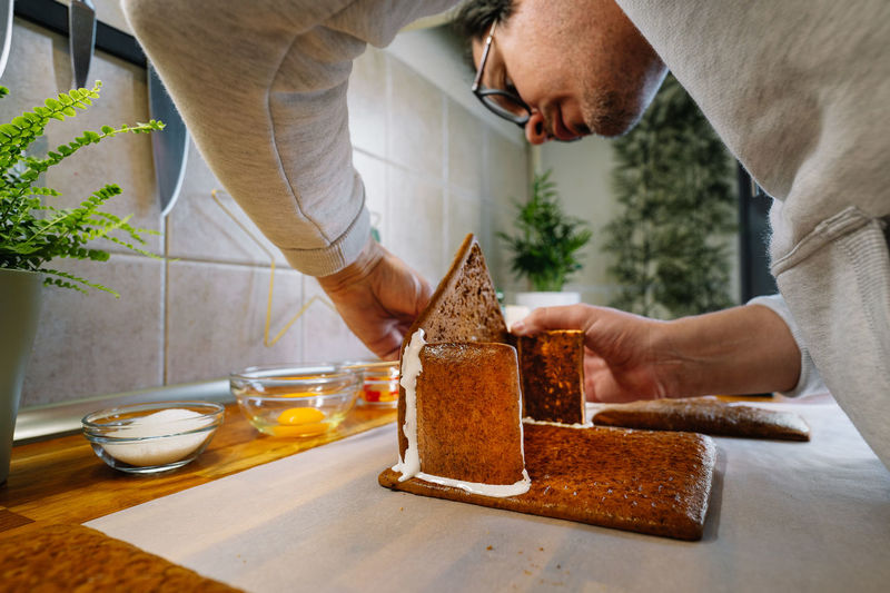 Midsection of man preparing gingerbread house on table in kitchen