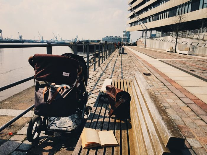 Book And Bag On Bench By Baby Carriage In City