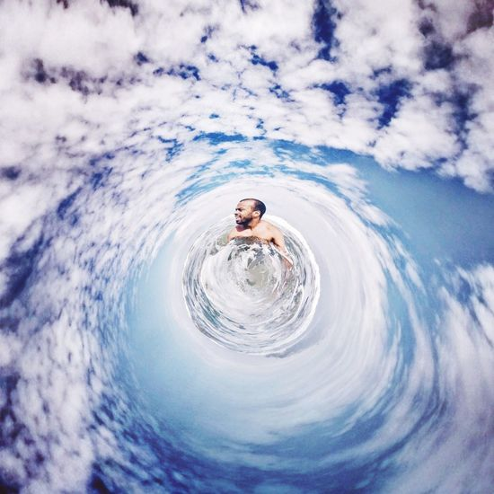 Little planet format view of man in sea against cloudy sky