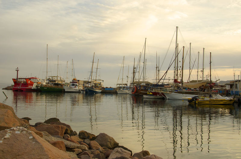 Fishing boats in the bay Nautical Vessel Transportation Water Mode Of Transportation Sky Moored Sailboat Cloud - Sky Harbor Pole Sea Nature Reflection Mast No People Tranquility Beauty In Nature Sunset Scenics - Nature Outdoors Marina Yacht Fishing Industry Port