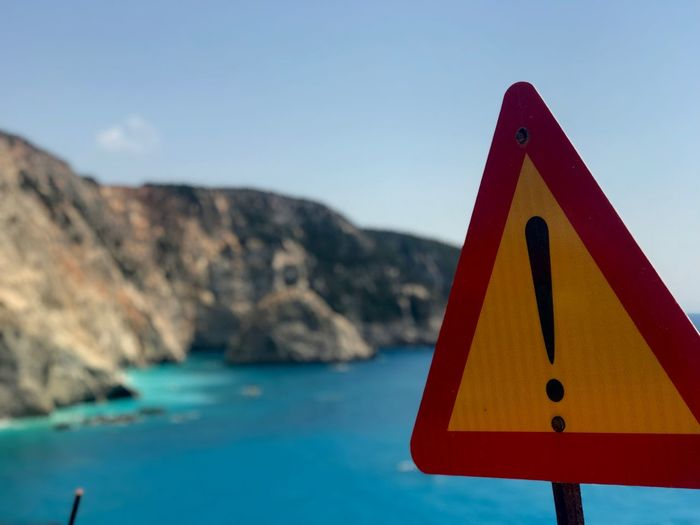 Close-up of road sign against sea and clear sky