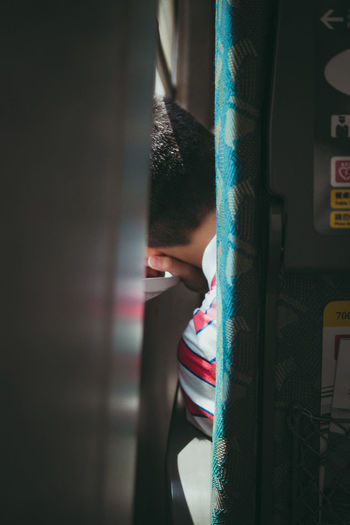 Rear view of boy sitting by window in train